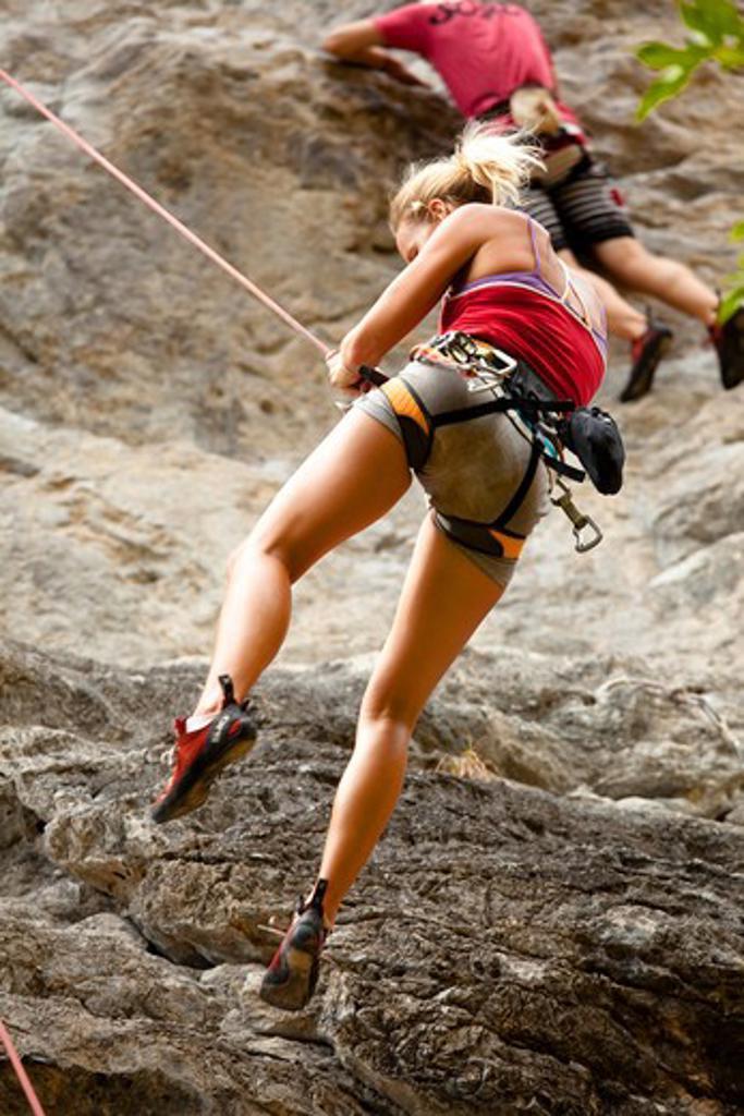 Woman rock-climbing : Stock Photo
