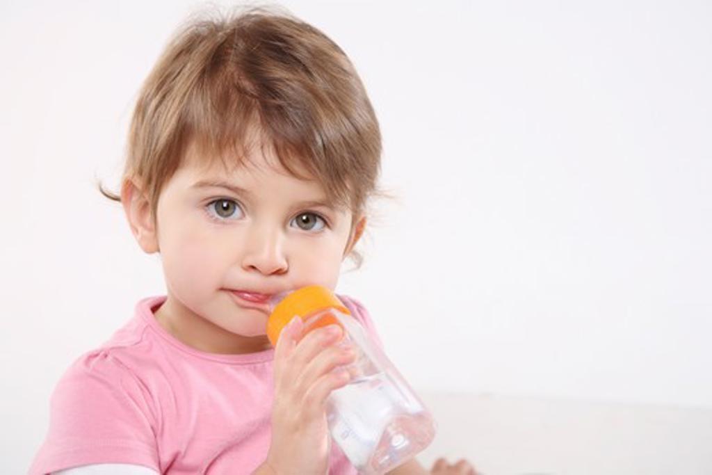 Stock Photo: 4252-2314 Little girl feeding bottle