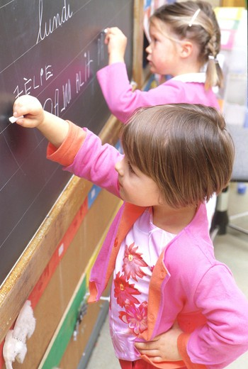 children inside girl school writing blackboard chalk class : Stock Photo