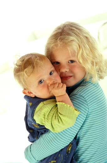 Stock Photo: 4252-25324 children inside girl portrait baby sister brother carrying tenderness sucking thumb