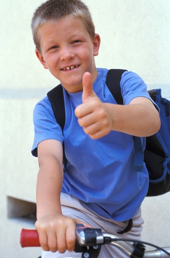 Stock Photo: 4252-25361 children outside portrait boy school bike school bag new school year expression thumb gesture hand smiling joy