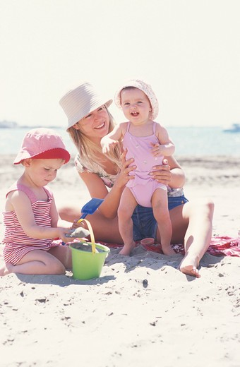family outside girl child woman sun protection mother mummy parent summer sea beach sand sitting stand up hat swimsuit t-shirt complicity game playing toys beach accessory bucket spade smiling holidays happiness : Stock Photo