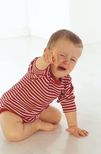 Stock Photo: 4252-25642 children inside baby sadness expression crying blond hair fall down movement hand shouting caprice portrait
