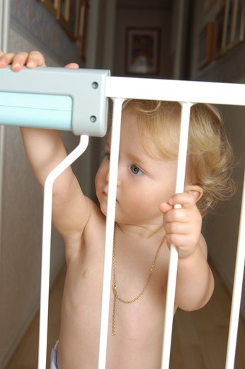 Stock Photo: 4252-26306 Baby girl standing behind safety barrier