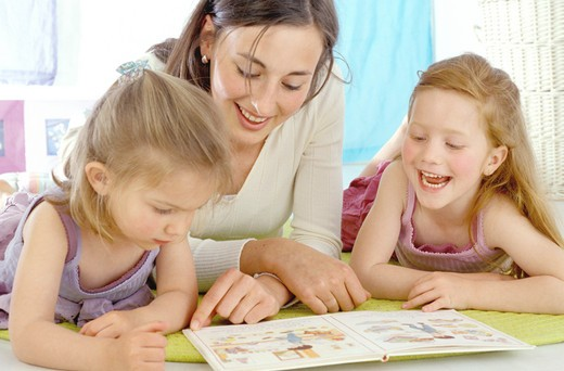Stock Photo: 4252-26419 Woman and two little girls looking at book