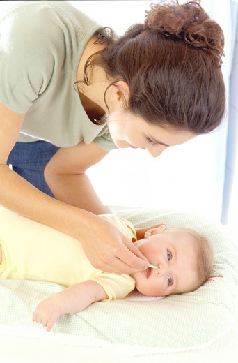 Stock Photo: 4252-26424 Woman cleaning nose of baby