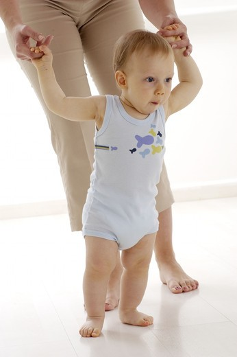 Baby boy first steps : Stock Photo
