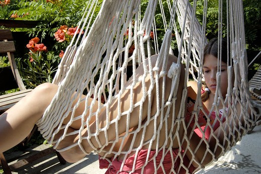 Teenager reading in a hammock : Stock Photo