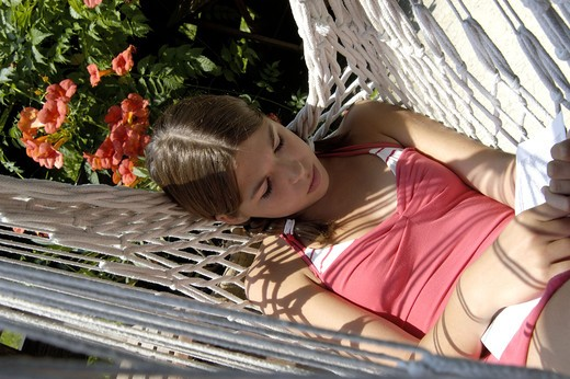 Stock Photo: 4252-27850 Teenager reading in a hammock