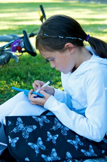 Stock Photo: 4252-32607 Little girl outdoor homework