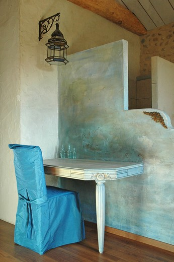 Stock Photo: 4252-35631 Table and chair with a blue cloth cover in front of a divinding wall painted with a blue patina into a bedroom