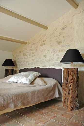 Attic bedroom with stone wall, tiled floor, bed with a classic bedhead and bedsides made with raw wood logs : Stock Photo