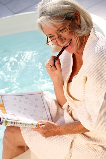 Stock Photo: 4252-9948 Senior woman crosswords