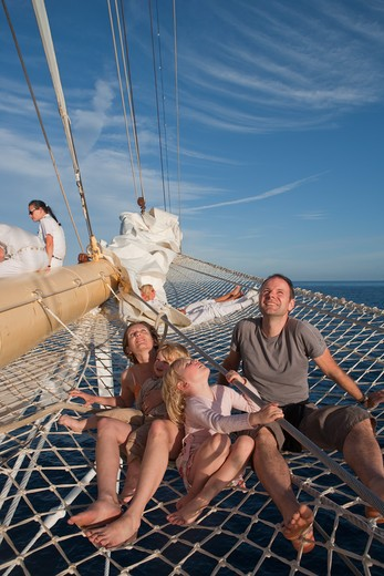 Young family in bowsprit net of sailing cruise ship Star Flyer (Star Clippers Cruises), Mediterranean Sea, near Bastia, Corsica, France, Europe [MR] : Stock Photo
