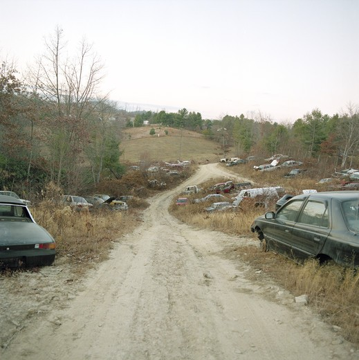 A collection of abandoned cars parked along winding road : Stock Photo