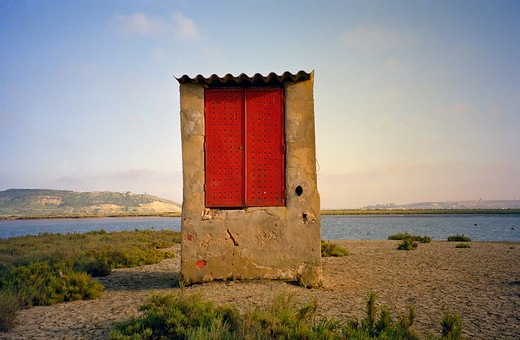 Small fishing hut with red shutters and corrugated iron roof, surrounded by mud, blistered by heat with late afternoon light, UK : Stock Photo