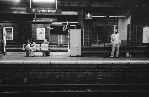A night scene in a platform of London Bridge train station, with a couple sitting on the bench, a black man with white suit and a suitcase standing on the right, London, England  : Stock Photo