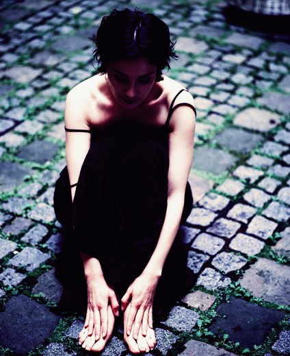 Sad Girl with a black dress sitting in a field, Paris : Stock Photo
