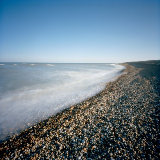 Rocky beach washed out by blue sea in evening bright light with blue sky. Kent, UK : Stock Photo
