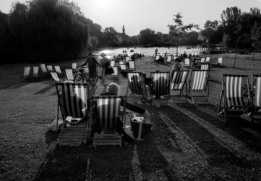 People sitting in deck chairs at sunset with lake and mosque in background. Regents Park, London, UK : Stock Photo