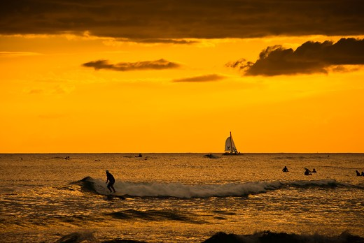 Stock Photo: 4260-1131 USA, Hawaii, Honolulu, Surfer catching wave just after sunset off Waikiki Beach