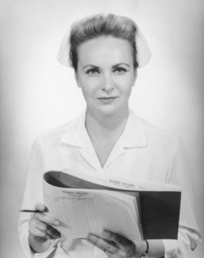 Stock Photo: 4267R-1145 Nurse holding medical records in studio, (B&W), portrait