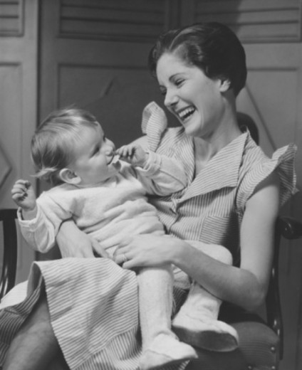 Stock Photo: 4267R-1158 Mother laughing with child (6-12 months) on laps, (B&W)