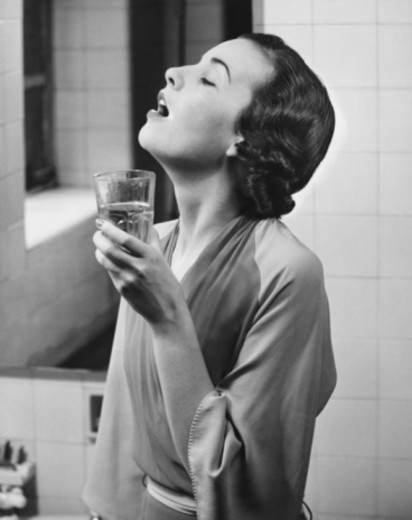 Stock Photo: 4267R-1260 Young woman in bathroom gargling water, (B&W)
