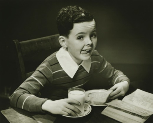 Boy (6-7) eating breakfast, (B&W), portrait : Stock Photo