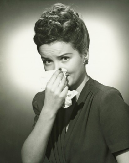 Woman blowing nose on tissue in studio, (B&W), portrait : Stock Photo