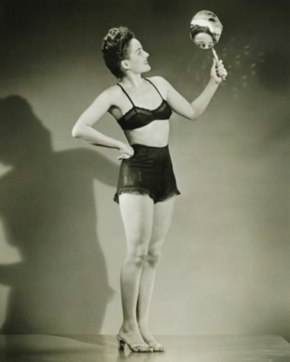 Woman in black underwear holding hand mirror in studio, (B&W) : Stock Photo
