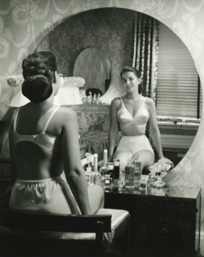 Stock Photo: 4267R-2790 Woman in underwear sitting in front of vanity table, (B&W), rear view