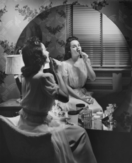 Stock Photo: 4267R-3284 Woman applying lipstick in front of vanity table (B&W)
