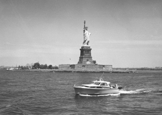 Stock Photo: 4267R-3852 Boat floating by Statue of Liberty, New York City, USA, (B&W)