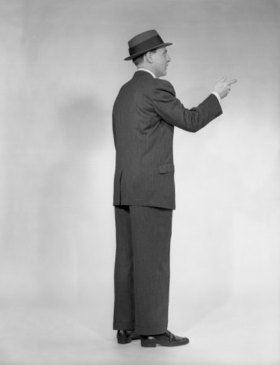 Man in full suit and hat pointing, side view, studio shot : Stock Photo