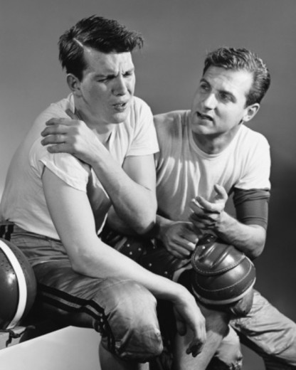 Stock Photo: 4267R-5209 Football player holding sore shoulder; trainer sitting beside him