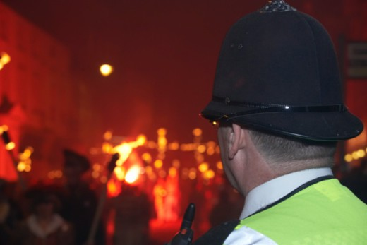 Stock Photo: 4268R-13038 Europe, Great Britain, England, Sussex, Lewes, Bonfire Night, policeman watching procession of revellers carrying crosses