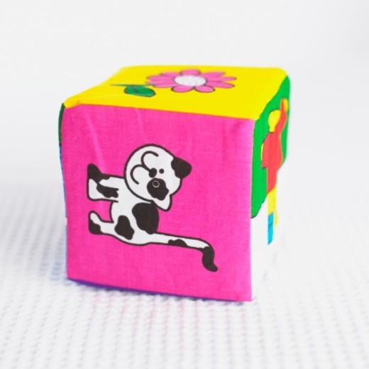 Soft cube toy with pictures of a cat on the sides. : Stock Photo