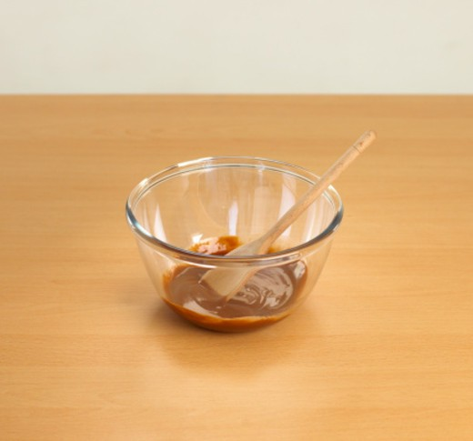 Bowl of melted chocolate with wooden spoon : Stock Photo