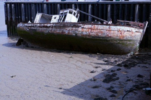 Abandoned fishing boat on beach next to jetty at tide out : Stock Photo