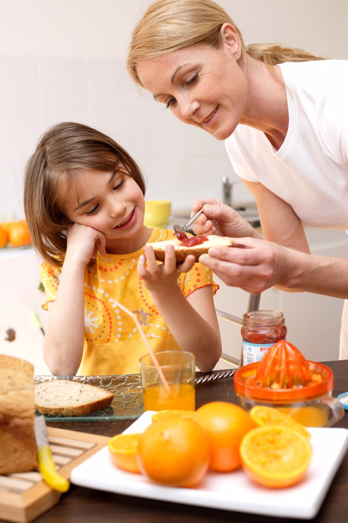 Child having breakfast or snack with her mother. : Stock Photo