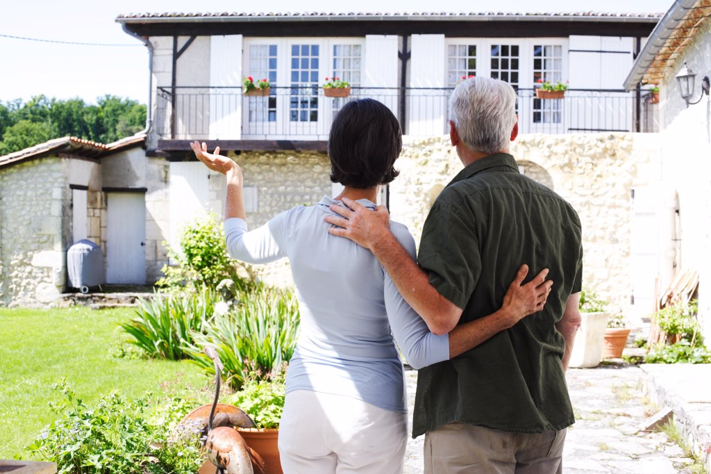 Senior couple looking at their house. : Stock Photo
