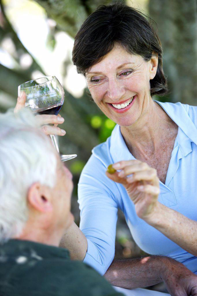 Senior couple drinking wine and eating olives. : Stock Photo