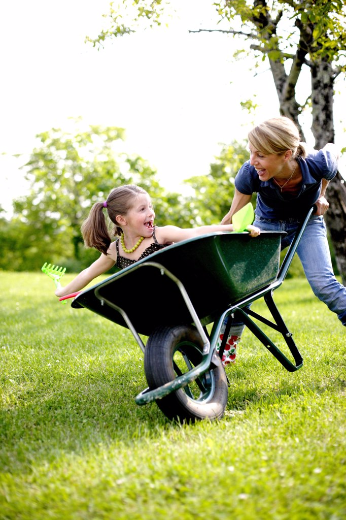 Stock Photo: 4269-11156 7 years old girl playing with her mother outdoors.