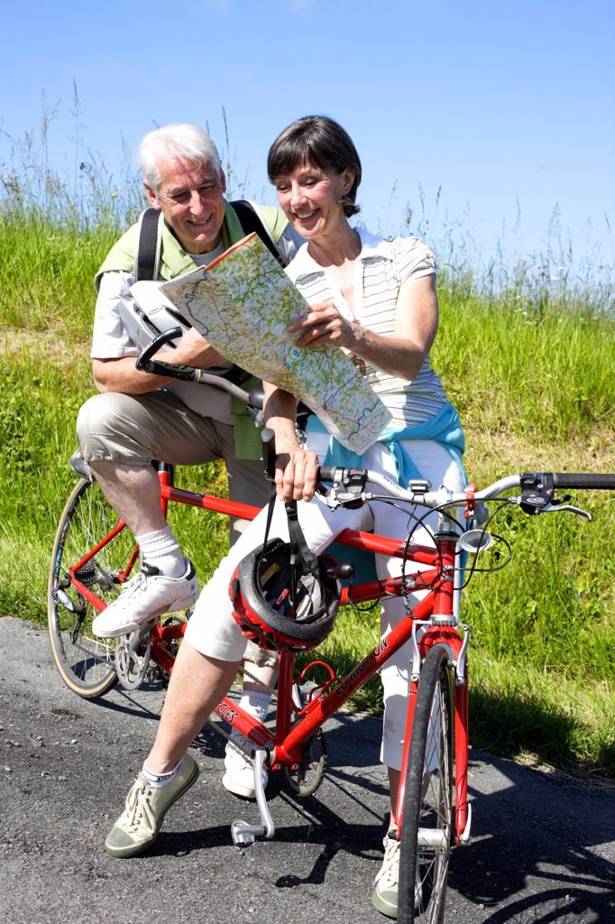 Senior couple riding tandem bicyle. : Stock Photo