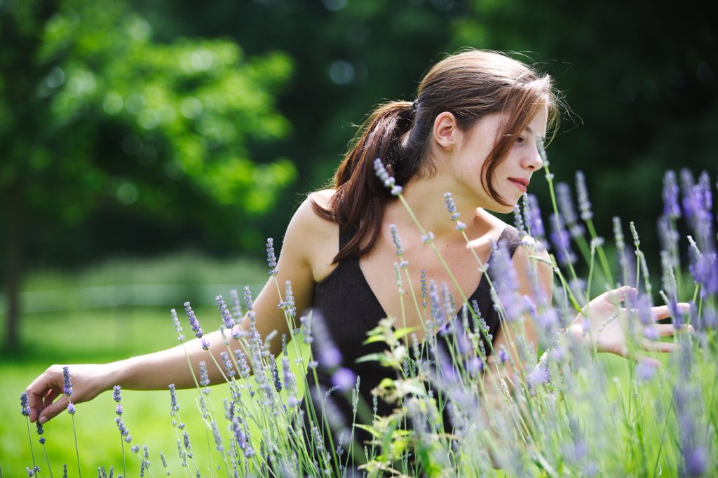 Young woman inhaling the scent of lavender. : Stock Photo