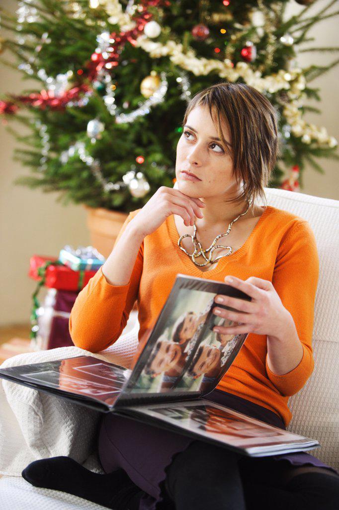 Stock Photo: 4269-11401 Woman watching photo album at Christmas.
