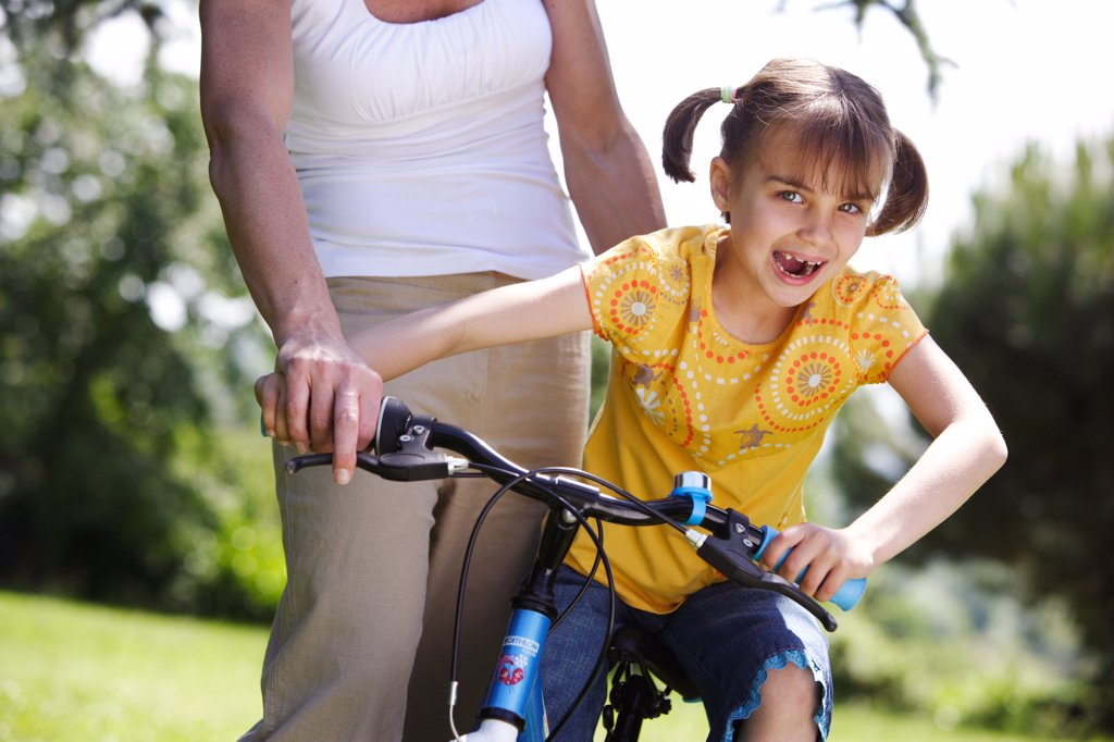 7 years old girl learning to ride a bicycle with her mother. : Stock Photo