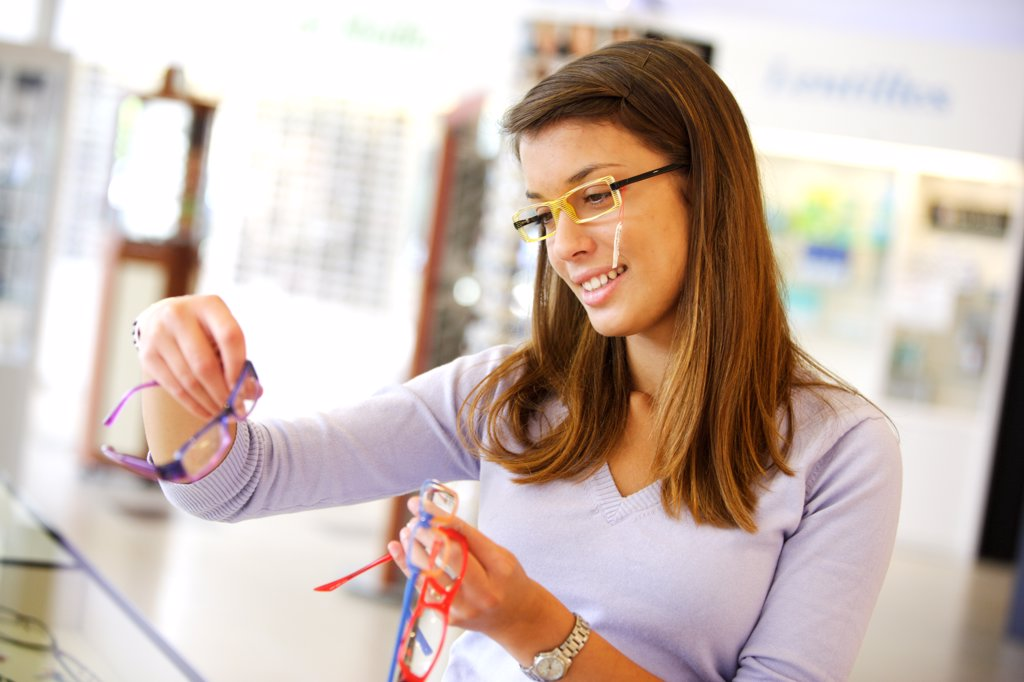 Stock Photo: 4269-11524 Young woman trying on prescription glasses at the optician.