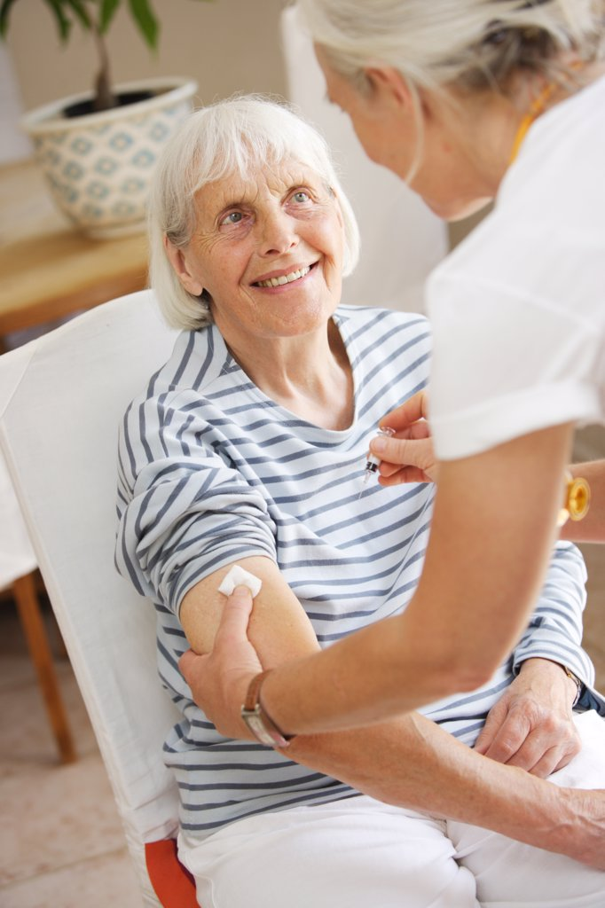 Stock Photo: 4269-11873 80 years old woman receiving vaccination against flu.